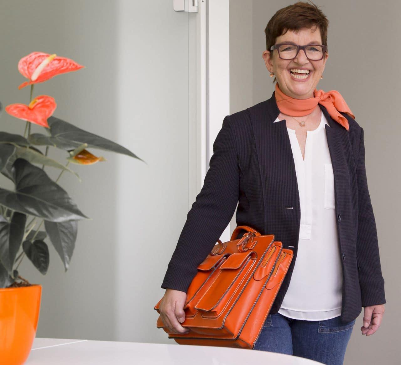 Portrait von Manuela Nikui mit Aktentasche im Büro